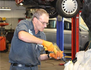 Car mechanic performing a vehicle repair