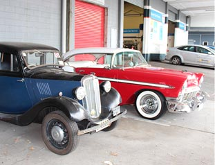 Two classic cars parked outside mechanics