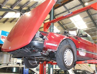 Red car on a car lift in service centre