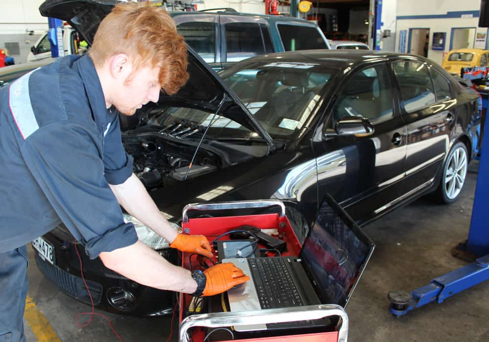 Diagnostic tools being used by a young mechanic during an affordable auto service