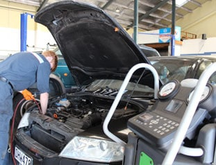 Young mechanic using diagnostics tools on car
