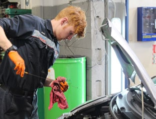 Young mechanic performing an oil check