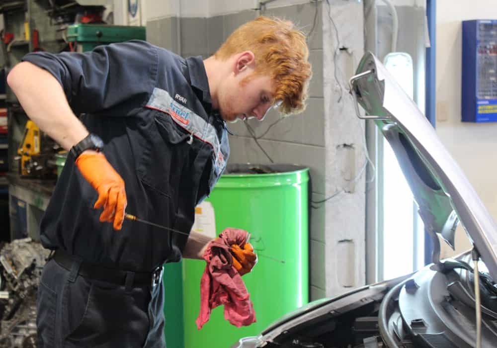 Young mechanic performing an oil check during a vehicle servicing.