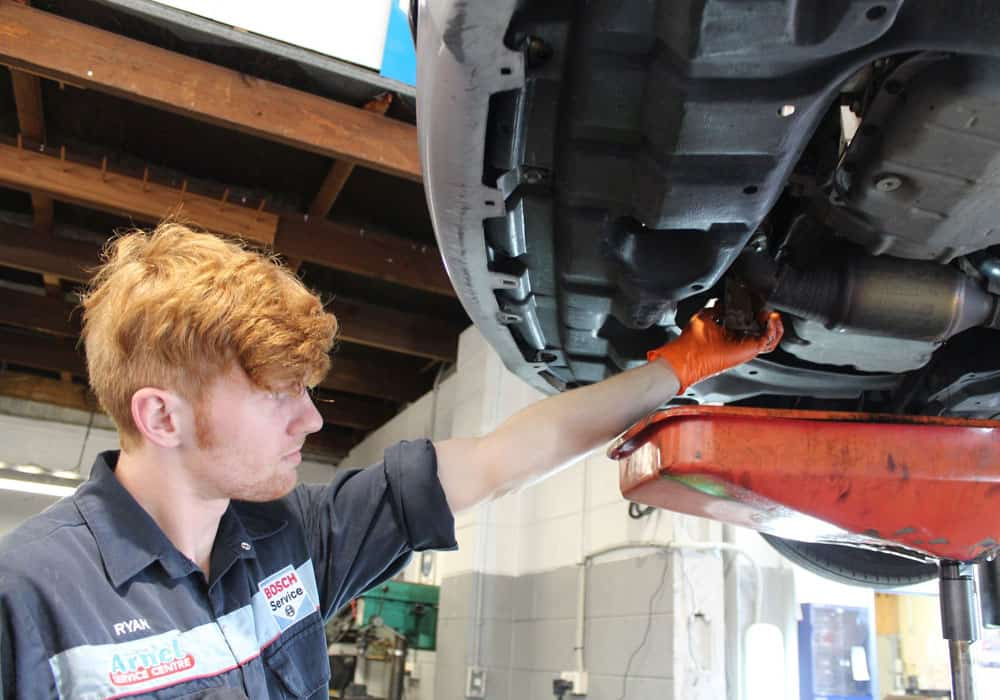 Young mechanic using diagnostics tools on car