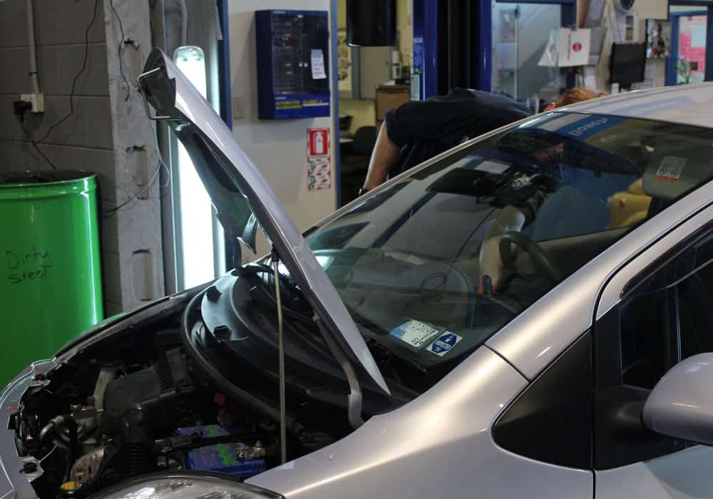 Car with hood raised for auto repairs in Hamilton